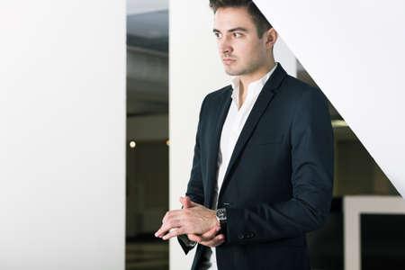 alumnus: Handsome young elegant alumnus of university. Standing in the middle of modern building