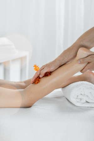lymphatic drainage: Womans leg isolated on a light background, woman having leg massage Stock Photo