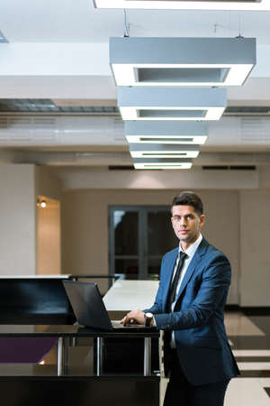 standing reception: Shot of a young professional standing at a reception desk, using his laptop Stock Photo