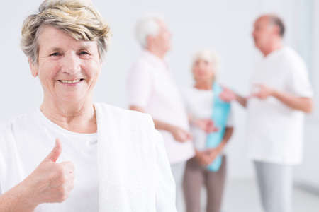 energetic people: Portrait of a smiling old woman at a gym, with a towel on her shoulder, holding her thumb up