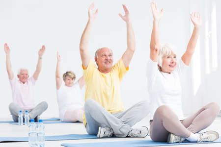 Ältere Männer und Frauen während der Fitness-Kurse, strecken ihre Arme, während sie mit gekreuzten Beinen auf Matten Übung sitzen