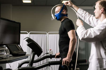 conduction: Doctor is setting up the necessary equipment for conduction of sport examination Stock Photo