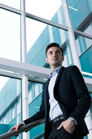 college life: Young elegant man after graduating ready to start new adult life. View from the bottom of student in suit on college Stock Photo