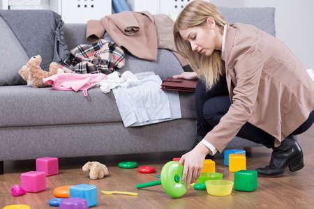 Junge Mutter, die ihr Kind das Spielzeug zu Hause zu reinigen. Frau nach der Arbeit müde Standard-Bild