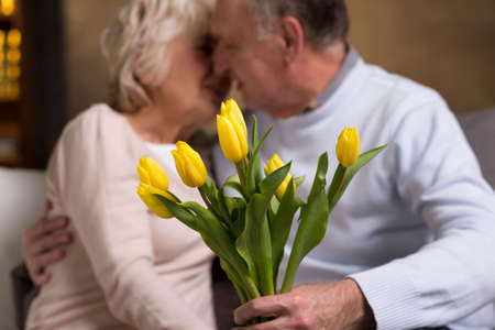 kisses: Older married couple in love kissing on a sofa. In the first plan  bunch of yellow tulips Stock Photo