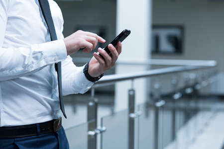 cell block: Close-up of a smartly-dressed man using a cell phone inside a modern office block