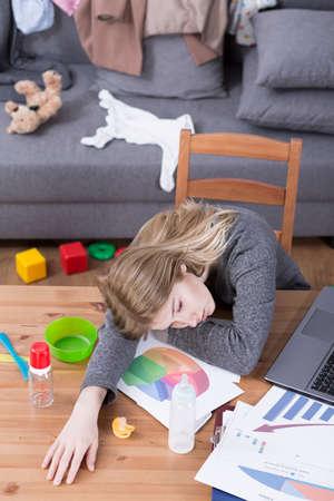 agotado: joven madre cansada que se sienta a la mesa en la habitación desordenada llena de juguetes del bebé. Mujer agotada después de todo el día