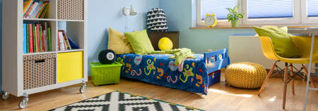 yellow walls: Child room with blue walls, single bed with colorful bedding, modern shelving unit and yellow chair Stock Photo