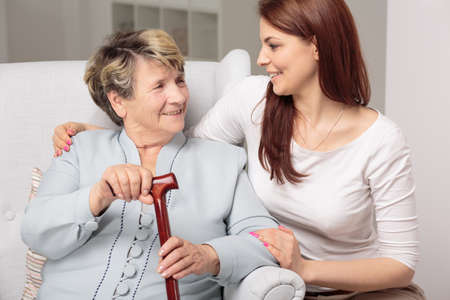 homecare: Granddaughter embracing her old and disabled grandma, senior lady holding walking stick