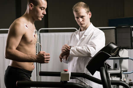 a medical examination: Doctor is supervising the athlete on a treadmill