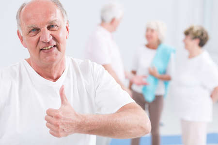 health club: Portrait of a senior man at a health club, holding his thumb up and smiling