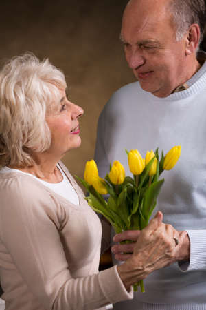 attachments: Elderly happy man giving flowers to his lovely wife for wedding anniversary