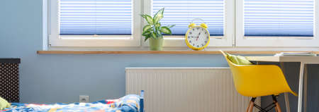 Study Desk: Blue interior with bed, yellow chair and desk, alarm clock and plant standing on a window sill