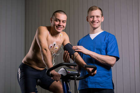 sportsmen: Sportsman is sitting on a stationary bike and the doctor measure his blood pressure