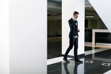 graduation suit: Young busy handsome man in suit talking the phone. Walking in modern building of university