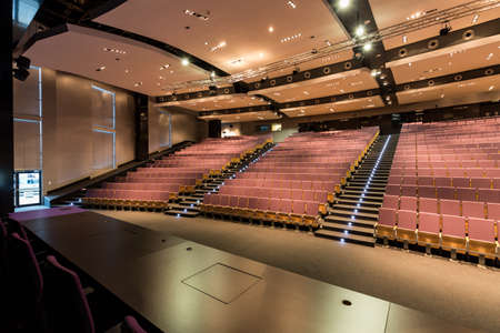 auditorium: Auditorium with long, dark table and rows of wood chairs Stock Photo