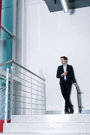 alumnus: Attractive elegant young alumnus standing in his old college