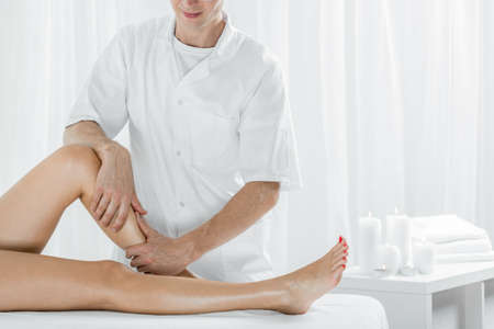 Professional masseur doing manual lymphatic drainage, light interior