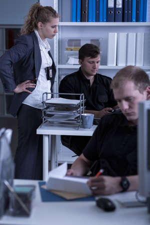police station: Shot of a detective checking on two policemen working at a police station Stock Photo