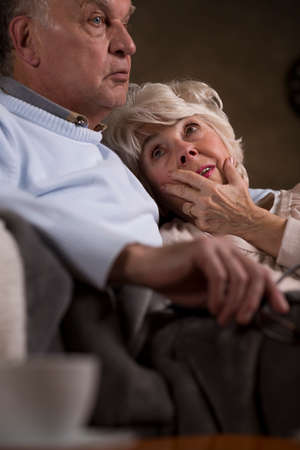 hugged: Older woman hugged to her loving husband. Marriage sitting together on a sofa