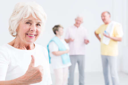 Portrait of an optimistic elderly woman at a gym giving a thumbs up sign, and her friends in the blurry background