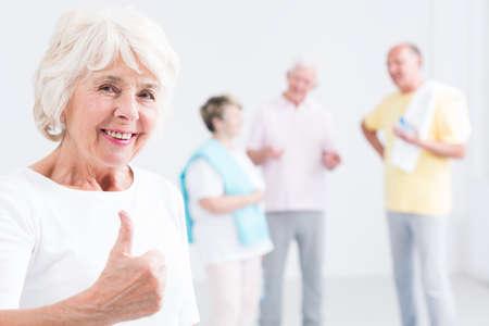 Portret van een optimistische bejaarde vrouw op een sportschool het geven van een duim omhoog te ondertekenen, en haar vrienden in de onscherpe achtergrond