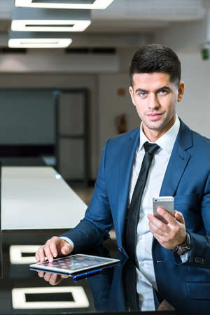 man business oriented: Close view of a young businessman at a worktop, using his tablet and mobile phone