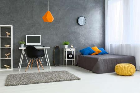 Útulná stylová ložnice určená pro dospívajícího chlapce. Šedé stěny a dřevěná podlaha. Na desce skateboard a police s dřevěnými modely
