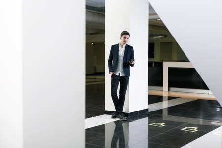alumnus: Young handsome man in suit walking around in corridor of his university. Holding a phone in a hand Stock Photo