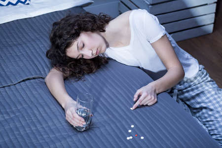 sleeping pills: Young woman with a glass of water in her hand, leaning on a bed where a few white tablets are spread