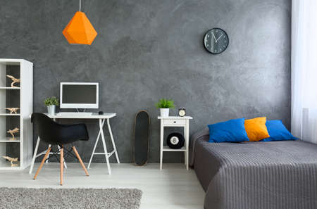 Bedroom with grey walls and grey bed with  colorful pillows and orange lamp. By the wall skate board and desk with computer Stock fotó