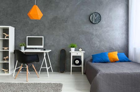 #57235403   Schlafzimmer Mit Grauen Wänden Und Grauen Bett Mit Bunten  Kissen Und Orange Lampe. An Der Wand Skate Board Und Schreibtisch Mit  Computer