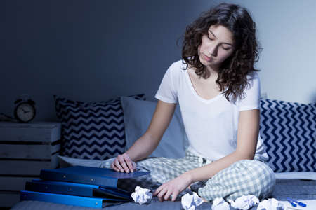 insomniac: Young woman sitting awake on her bed in the middle of the night, surrounded by crumpled sheets of paper Stock Photo