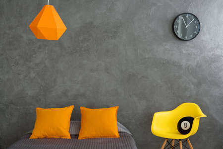 additions: Bedroom with grey walls and bed and colorful additions. Orange pillows, lamp and yellow chair in grey dark room