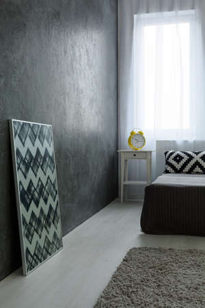 additions: Photo of grey simple room with black and white elements. In the corner big bed and nightstand with clock alarm