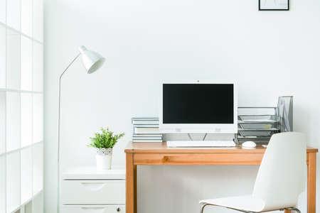 나무 테이블과 흰색 컴퓨터와 깔끔한 홈 오피스. 흰 벽 밝은 방 스톡 콘텐츠