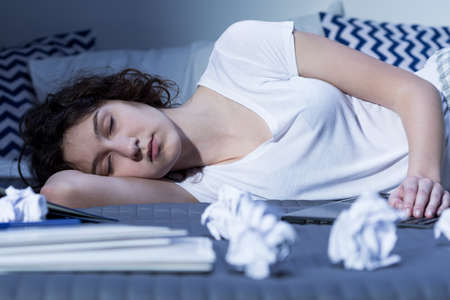insomniac: Close-up of an exhausted young woman sleeping in her bed next to a laptop, surrounded by crumpled pieces of paper
