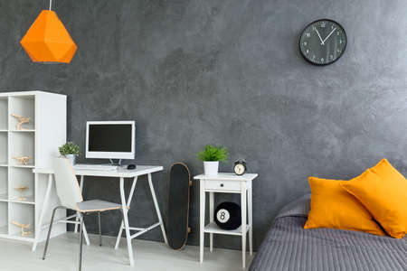 nightstand: White desk with computer, shelf and nightstand near grey bed with orange pillows Stock Photo