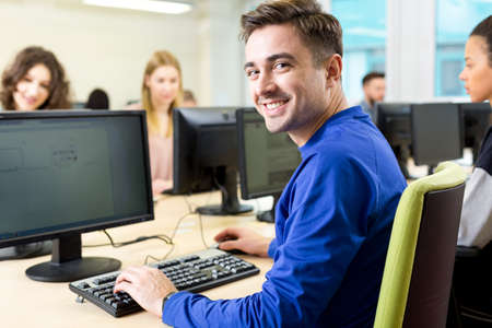 computer science: Shot of a happy student using a computer in a computer room Stock Photo