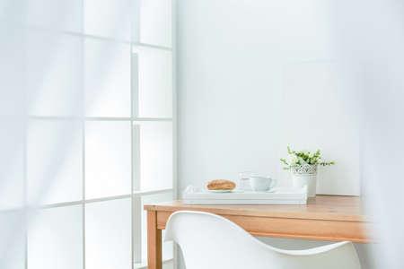 Houten eettafel in de hoek van de kamer. Op het witte bakje met bladerdeeg en koffie Stockfoto
