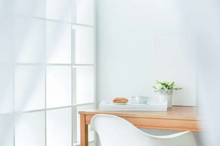 Wooden dining table in the corner of room. On it white tray with puff pastry and coffee