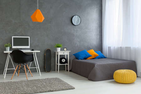 boy bedroom: Stylish designed boy teenagers bedroom with grey walls and white furniture and colorful decorations