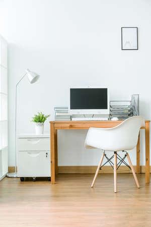 Amplia habitación con suelo de madera con un pequeño espacio para el trabajo. Por la mesa de madera de la pared con el ordenador