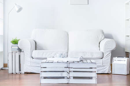 living style: Bright living room with comfortable white sofa. In front of it coffee table made of old wooden boxes