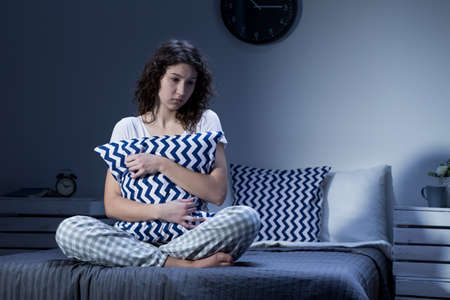deprivation: Sleepless and depressed young woman in pyjamas sitting on a bed and holding a cushion