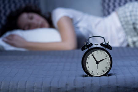 sleeping pills: Close-up of a black, vintage alarm clock on a bed where a young woman is lying in the blurry background