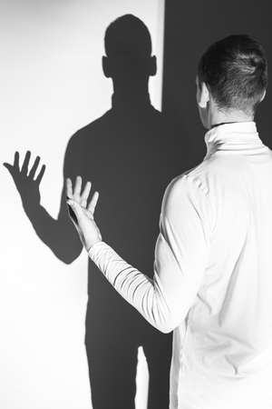 psychopath: Shot of a young man talking to his shadow Stock Photo