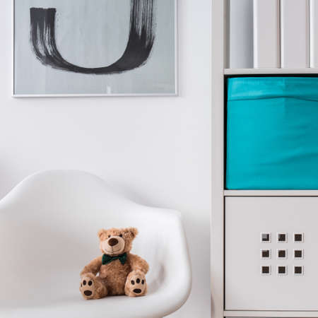 modern apartment: White wood regale and chair with toy in child room Stock Photo
