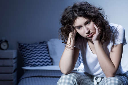Primo piano di una giovane donna in pigiama seduto insonne sul bordo del suo letto nel cuore della notte
