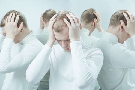 psychopath: Image of a young man holding his head